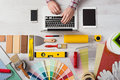 Professional decorator working at desk s hands his and typing on a laptop color swatches paint rollers and tools on work table top Royalty Free Stock Photos