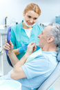 Professional dentist looking at mature patient holding mirror