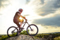 Professional Down Hill Cyclist Resting with Bike on the Rock at Sunset. Extreme Sport. Royalty Free Stock Photo