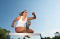 Professional female hurdler in action Royalty Free Stock Photos