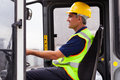 Professional forklift operator middle aged warehouse worker operating Stock Photos