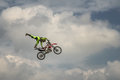 Professional Freestyle Motocross rider carries out a trick in a jump with the motorcycle on background of the blue cloud sky. Germ Royalty Free Stock Photo