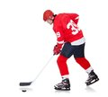 Professional hockey player skating on ice Stock Photos