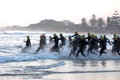 Professional ironman triathletes swimming start of the professionals running into the sea water at specsavers south africa Stock Photo