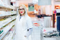 Professional pharmacist standing in pharmacy drugstore and smiling. Details of pharmaceutical industry Royalty Free Stock Photo