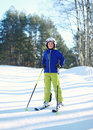 Professional skier child boy in sportswear helmet on ski winter, snowy day on hill mountain over forest Royalty Free Stock Photo