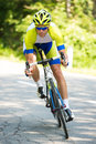 Professional sport Cyclist riding a bike on an open road down the hill on a hot summer day Royalty Free Stock Photo