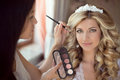 Professional stylist makes makeup bride on the wedding day beau beautiful smiling blond women with long curly hair style Royalty Free Stock Photography