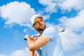 Professional swing low angle view of young and confident golfer swinging his driver and looking away with blue sky as background Royalty Free Stock Photography