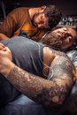Professional tattoo artist showing process of making a tattoo in Royalty Free Stock Photo