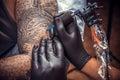 Professional tattooer showing process of making a tattoo in tatt Royalty Free Stock Photo