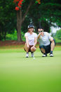 Professional teaching young woman golfer Stock Images