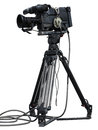 Professional video camera set on a tripod isolated over white background Royalty Free Stock Images