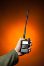 Professional walkie talkie radio in hand on orange background Stock Photos