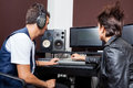 Professionals mixing audio together in recording young men and female studio Stock Photos
