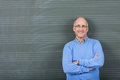 Professor with hands folded standing against chalkboard portrait of confident male in classroom Stock Images