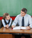 Professor and little girl looking at each other at mature desk in classroom Royalty Free Stock Photo