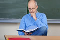 Professor reading book at desk in classroom male while sitting Stock Photos