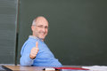 Professor showing thumbs up gebaar bij bureau Stock Foto