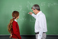 Professor teaching mathematics to female student side view of male on board in classroom Stock Photography