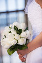 Profile of bride holding bouquet a in white wedding dress a white roses Stock Photo
