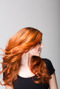 Profile of a cool redhead flicking her hair woman gorgeous long wavy so that it is flying loose around face Stock Photos