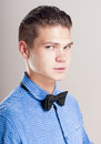 Profile of gallant man in the blue shirt with black bow tie over gray background Stock Photos