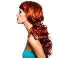 Profile portrait of a woman with long red hairs fashion model curly hairstyle isolated on white Stock Photo