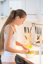 Profile portrait of a young woman making salad on the kitchen Royalty Free Stock Photo