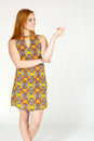Profile of smiling girl. She points with her fingers. Redheaded Royalty Free Stock Photo