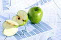 Profit concept closeup of half and whole apple on paper background with chart Royalty Free Stock Image
