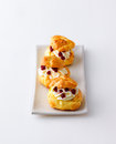 Profiteroles with cream and cranberries Royalty Free Stock Images