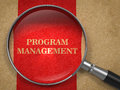 Program management concept through magnifying glass on old paper with red vertical line background Royalty Free Stock Photography