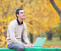 Programmer with notebook sitting in autumn park Stock Images