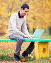 Programmer with notebook sitting in autumn park Stock Photography