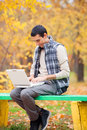 Programmer with notebook sitting in autumn park Royalty Free Stock Photo