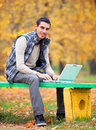 Programmer with notebook sitting in autumn park Royalty Free Stock Photography