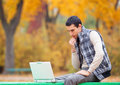 Programmer with notebook sitting in autumn park Royalty Free Stock Photos