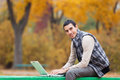 Programmer with notebook sitting in autumn park Stock Photos