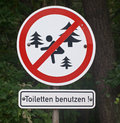 Prohibition sign in closeup for of defecation in the forest Stock Photo