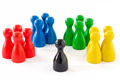Project coordinator four groups of game figurines and a black one in the middle concept team coordination leader Royalty Free Stock Photos