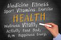 Promoting good health text in yellow uppercase letters on black chalkboard with related topics like wellness vitality gym Royalty Free Stock Photography