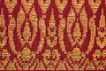Prong pattern thai silk a beautiful piece of very fine of golden on red and black background Stock Images