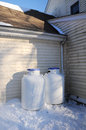 Propane tanks two gallon white for heating on the outside of a house on a cold snow covered ground Royalty Free Stock Photography
