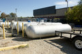 Propane tanks wait for transport beside a flatbed trailer Royalty Free Stock Photography