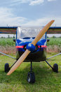 Propeller of a fixed wing aircraft and nose blue single engine parked in rural field closeup view Stock Photos