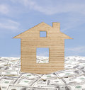 Property insurance concept model house in a pile of dollars Stock Image
