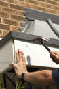 Property maintenance making repairs to canopy fascia board Stock Photos
