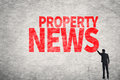 Property news asian business man write words on wall Royalty Free Stock Image