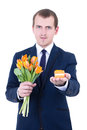 Proposal young man holding gift box in suit with wedding ring and flowers isolated on white background Royalty Free Stock Photography